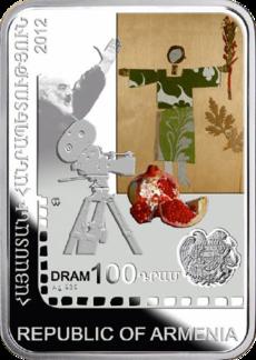 """Eine hochkant stehende rechteckige Münze. Darauf sind eine Kamera, ein Bild mit einem grün gekleideten Mann, ein aufgeschnittener Granatapfel und ein Wappen abgebildet. Dazu der """"Republic of Armenia"""" und """"DRAM100"""""""