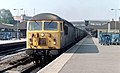 A class-56 locomotive heads through Leicester station with a train of coal wagons, Nigel Tout, July 1985.jpg
