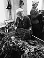 A female worker tears large pieces of salvaged clothing into strips at a salvage depot in Britain during April 1942. D7438.jpg