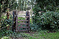 Abbess Roding - St Edmund's Church - Essex England - churchyard west gate in ivy hedge.jpg