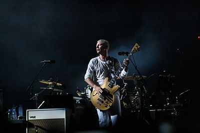 Adam Clayton playing the bass guitar on stage in a stadium