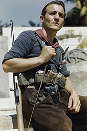 Man with rifle over his shoulder and ammunition in a belt