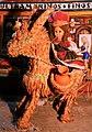 Andalusische Puppe auf Bastesel mit Terracotta-Krügen vor keramischem Lebensmittelgeschäft.jpg
