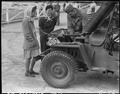 "Arcadia, California. Two young evauees of Japanese ancestry watch an army mechanic repair a ""Jeep"" . . . - NARA - 537448.tif"