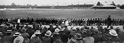 An early 20th-century cricket match, watched by a large crowd