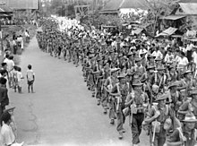 A large body of soldiers in column of route march through a town