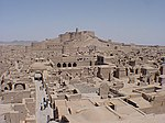 View over a large ruined city colored uniformly in a grey-brown tone. In the background there is a castle in overlooking the surrounding city.