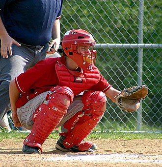 "Catcher - A catcher in customary squatting position (wearing a ""hockey-style"" mask) prepares to receive a pitch."