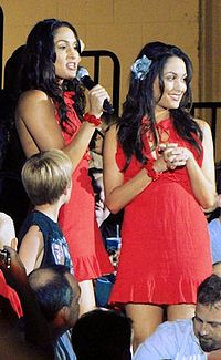 Indentical female twins with long black hair standing in a crowd. Both are wearing short red dresses and have a blue flower in their hair, although their wear the flower on the opposite side to the other. The woman on the left is talking into a microphone.