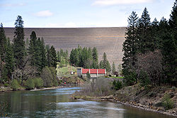 A large dam rises high above a red-roofed building at its base. A large river flows away from the base of the dam.
