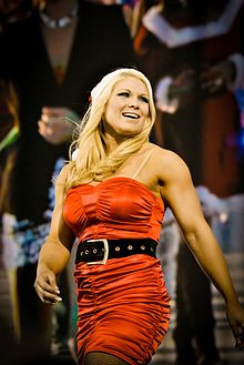 A blonde haired woman wearing a red santa hat and red red with a black belt.