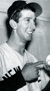 A candid shot of a young man in a baseball uniform, smiling and holding a baseball