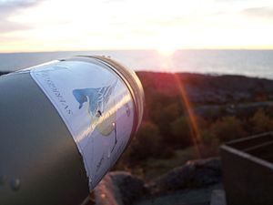 Swedish Ornithological Society - Birdwatching in sunrise, a spotting scope with a stcker from the Swedish Ornithological Society.