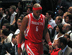 A black man wearing a red and white basketball uniform and matching red headband walks to the bench during a basketball game with his head down.