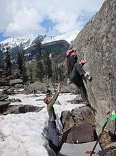 Un grimpeur sur un bloc en extérieur et une personne à côté du crash-pad qui fait une parade.