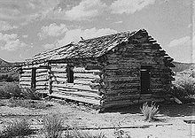 Black-and-white photo of log cabin with thatched roof