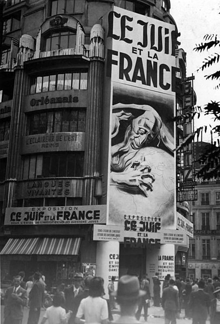 "Poster above the entrance of an anti-semitic exposition called ""The Jew and France"" Bundesarchiv Bild 146-1975-041-07, Paris, Propaganda gegen Juden.jpg"