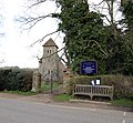 Bush End, Essex, England ~ St John Evangelist exterior ~ church and sign from southwest 02.jpg