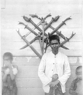 Klewang - An Acehnese collection of Kris (hung vertically) and Klewang (hung diagonally) during the Dutch colonial period, c. 1893–95.
