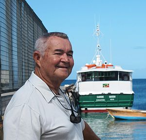 Arthur Anslyn - In 2014, Captain Arthur Anslyn standing at the port in Nevis with the stern of MV Carib Queen visible behind him; he was Captain of that ferryboat for 19 years.