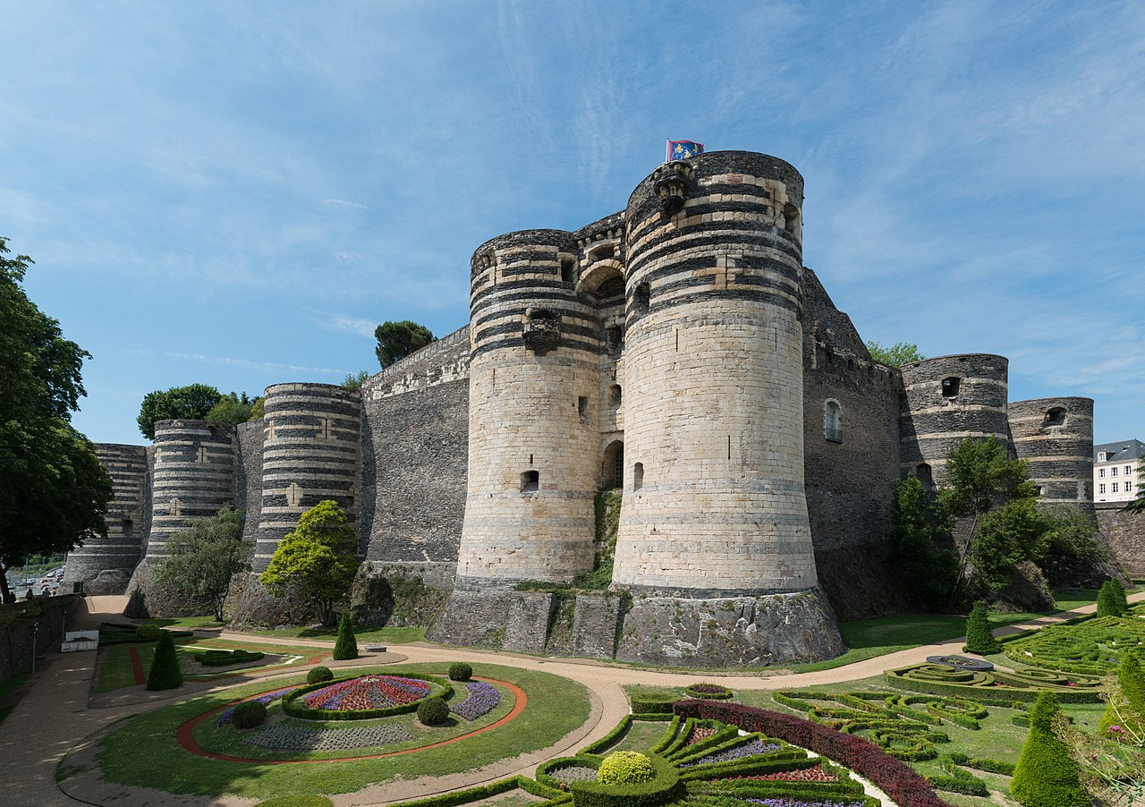 the huge stone walls of Château d'Angers in France with colourful gardens in the foreground