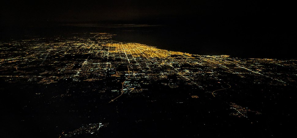 Night aerial view of Chicago and vicinity, from Gary, Indiana, on the right, through Waukegan, Illinois, Kenosha, Wisconsin, Racine, Wisconsin and Milwaukee, Wisconsin in the distance at upper left.