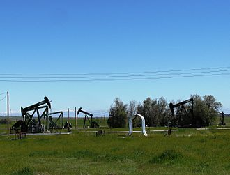 Coalinga Oil Field - Oil wells and steam apparatus along Derrick Road in the western portion of the Coalinga field. The vertical loops are steam pipes; steam is pumped into the underground heavy oil deposits to help them flow more freely.
