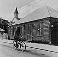 Collectie Nationaal Museum van Wereldculturen TM-20006243 Vrouw op de fiets voor een huis bij de Methodistenkerk in de Voorstraat Philipsburg Boy Lawson (Fotograaf).jpg