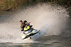 Couple of teenagers riding a personal watercraft splashing on the Mekong in Laos.jpg