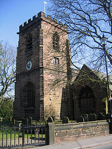A square castellated tower viewed from one corner, with its front, incorporating a clock and an arched entrance, in shadow. The main church building, about half the height of the tower, is to the right and is connected to the tower.