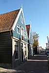 foto van Houten huis met houten topgevel boven een bakstenen pui