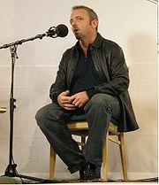 Photographie de Dennis Lehane, assis, parlant dans un micro, lors de la présentation de l'un de ses films en 2006