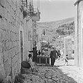 Een vrouw en een man in het dorp Ain Karem die een kist versjouwen naar een vrac, Bestanddeelnr 255-1195.jpg