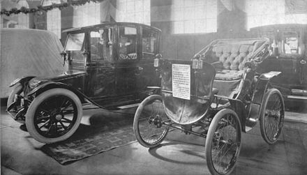 An EV and an antique car on display at a 1912 auto show Electric car and antique car on display at 1912 auto show.jpg