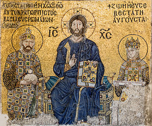 A mosaic with a background of gold depicts a seated Christ Pantocrator. A woman stands to his left and her husband stands to his right.
