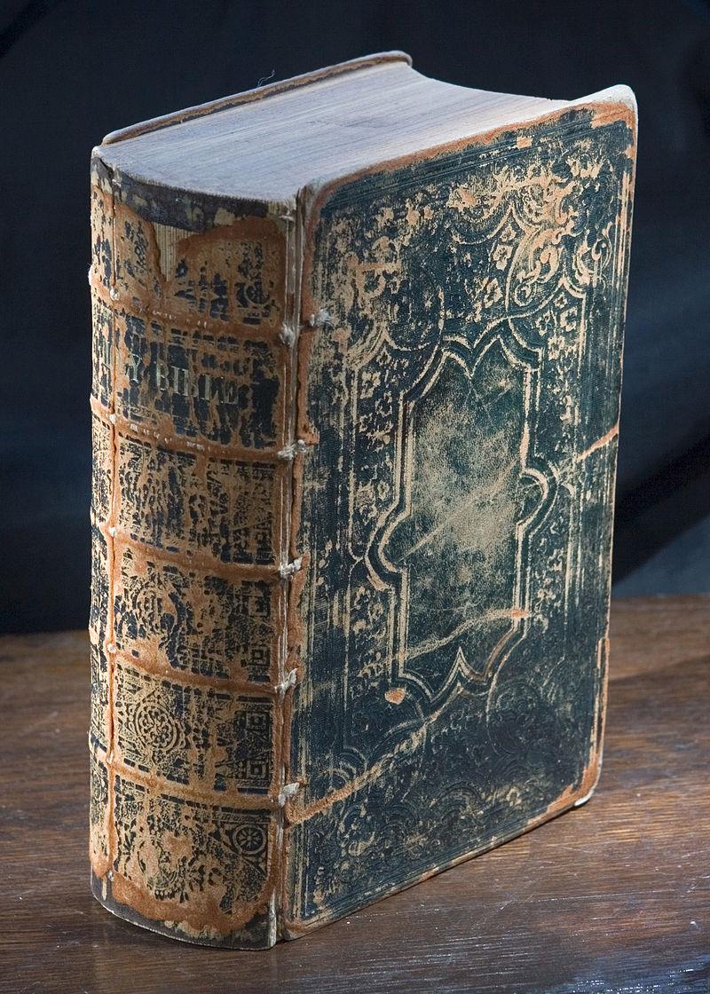 Photographie d'un livre dont la couverture est noire et usée, sur la tranche il est indiqué HOLY BIBLE