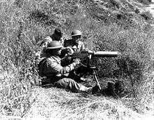 Three soldiers behind a M1917 Browning machine gun while training in a field in California