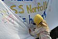 Flickr - Official U.S. Navy Imagery - A girl signs a welcome home sign for USS Norfolk..jpg