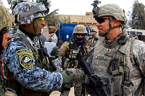 Iraq War order of battle, 2009 - A U.S. Army officer from the 4th Infantry Division with an Iraqi policeman in January 2009.