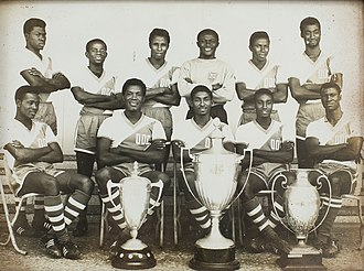 Ghana national football team - Black Stars members in the 1960s pose with some of Ghana's successive international football trophies won.