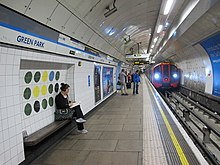 An underground station platform with white tiled walls, a white panelled ceiling arching over the track. The tiled a recess behind a platform seat features a design of twelve coloured circles arranged in a 4 by three grid; mostly dark green, but with three yellow, two black and one blue circles.