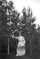 Helporträtt av en kvinna i vit klänning och hatt bland tallar - Nordiska Museet - NMA.0056418.jpg