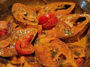 Ilish - Ilishi maachha curry with ginger mustard garlic paste in tomato seasoning in Odisha style in Oriya cuisine.