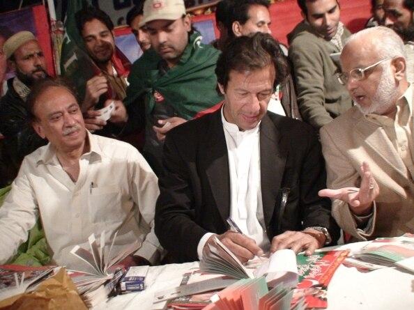 Imran Khan giving autographs