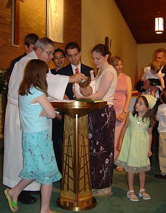 Infant baptism - Water is poured on the head of an infant held over the baptismal font of a Roman Catholic church