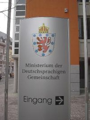 German-speaking Community of Belgium - The entrance of the ministerial building of the German-speaking Community shows the coat of arms of the Community, which has the nine cinquefoils arranged differently from the flag, and also sports a royal crown.