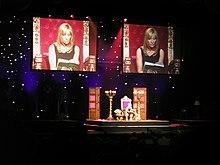 Une femme blonde est installée dans un grand fauteuil doré, sur une scène éclairée, et lit un livre devant un public plongé dans le noir. Deux écrans en fond de scène retransmettent des images identiques de la lectrice en plan rapproché.