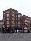 foto van Woonblok met arbeiderswoningen en winkels