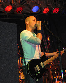On stage, a man is holding a microphone to his mouth with his right arm while his left hand clasps the neck of a guitar. He is mostly bald headed, staring forward, with five coloured lights above and band equipment obscured, behind.