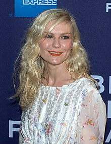 Kirsten Dunst is pictured outdoors; she has wavy red hair and is wearing a